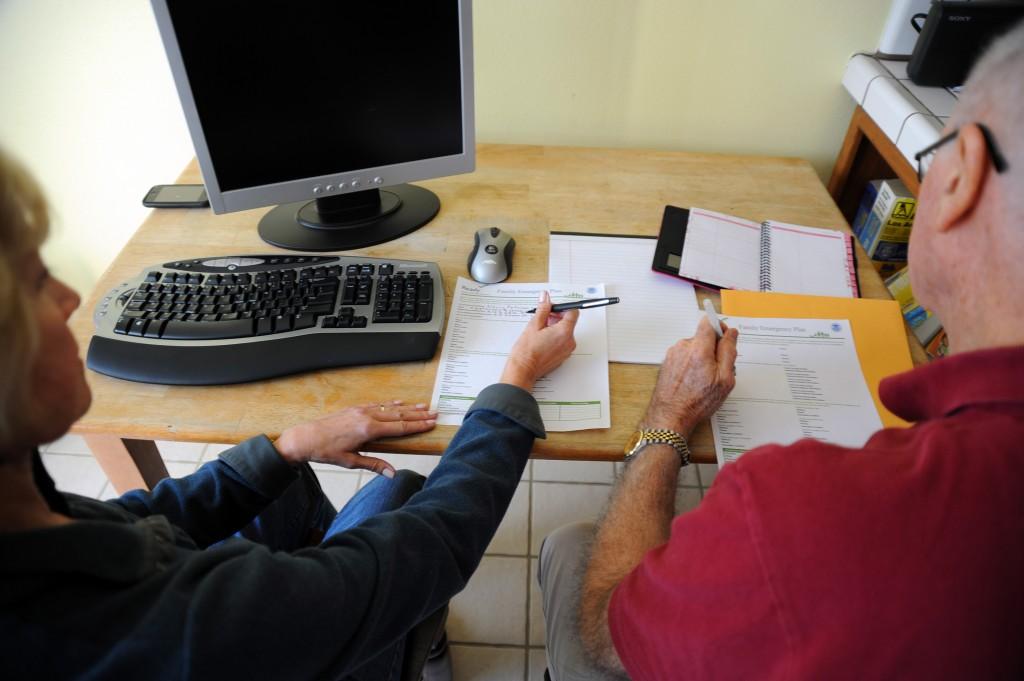 Senior couple at desk making emergency plan.